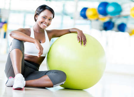 Happy woman at the gym with a Pilates ball and smiling photo