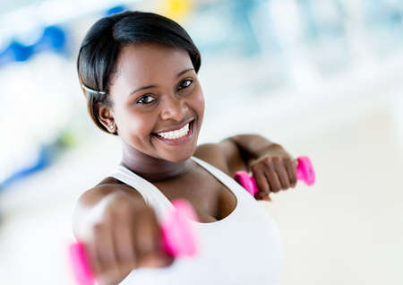 woman lifting weights: Strong woman weightlifting at the gym working out Stock Photo