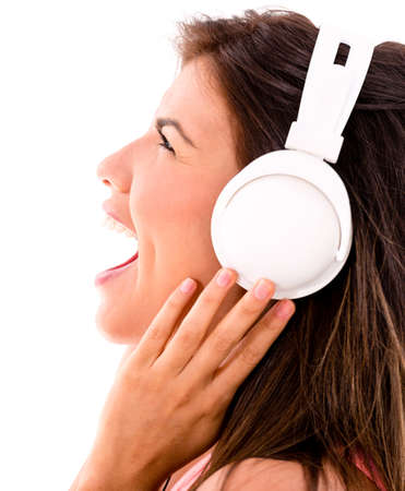 Happy woman loving music headphones and singing - isolated over white photo