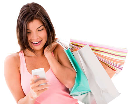 Happy shopping woman texting on her cell phone - isolated over white photo