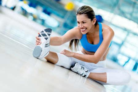 estiramientos: Hermosa mujer de estiramiento en el gimnasio buscando feliz