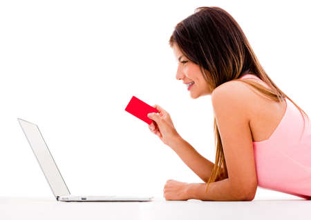online payment: Woman online shopping with her laptop - isolated over white