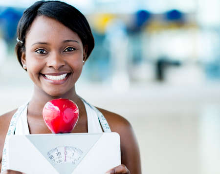 scales thin: Healthy eating woman holding scale and an apple