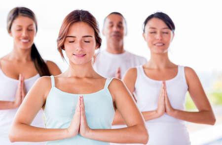 mujer meditando: Grupo de personas meditando en una clase de yoga
