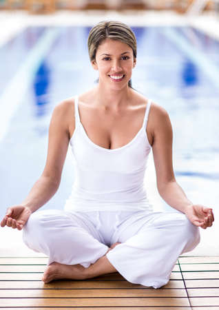 Woman practicing yoga by the pool and looking happy  photo