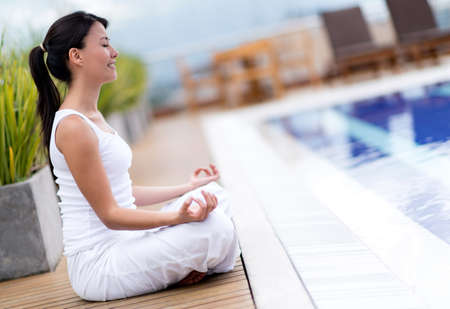 Yoga woman meditating by the pool looking very relaxed photo