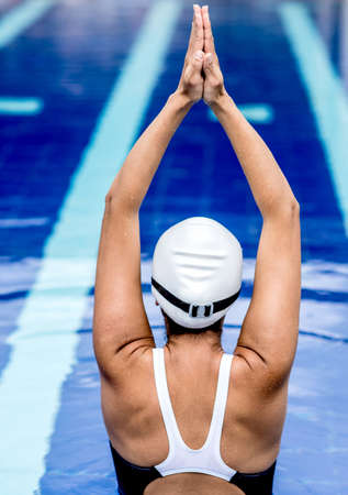 Female swimmer stretching her back in the pool  photo