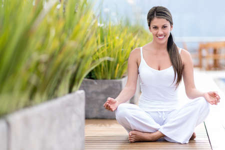 Yoga woman sitting on the floor and smiling outdoors  photo