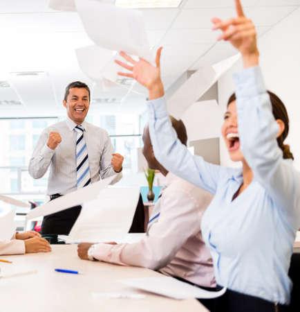 personas festejando: Equipo de negocios exitoso celebrando en la oficina en una reuni�n