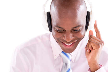 Business man listening to music with headphones - isolated over white  photo