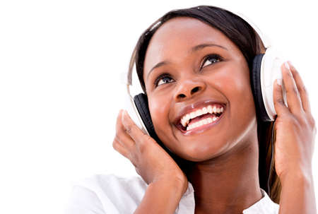 Happy woman listening to music with headphones - isolated over white photo