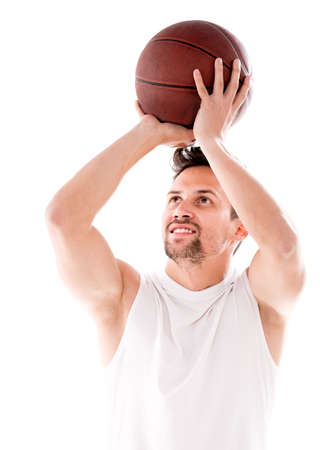 Male basketball player shooting the ball - isolated over black photo