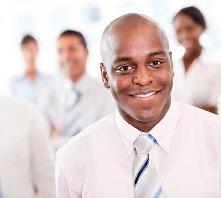 black business man: Heureux l'homme d'affaires noir au bureau souriant Banque d'images
