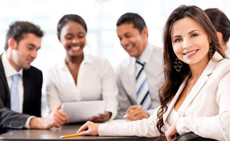 casual business team: Successful business woman at the office with her team Stock Photo