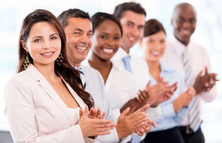 applauding: Successful business team applauding at the office looking happy