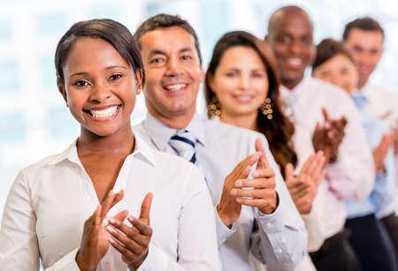 personas celebrando: Unidad de negocio acertada que aplauden en la oficina