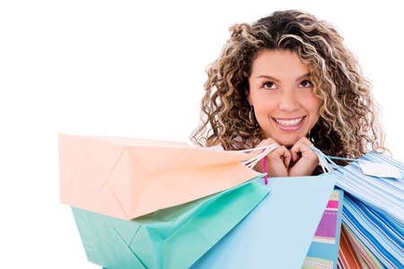 Thoughtful shopping woman hoding bags - isolated over white background photo