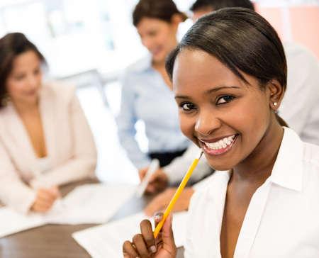 jovenes empresarios: Exitosa mujer de negocios negro en la oficina que parece muy feliz Foto de archivo
