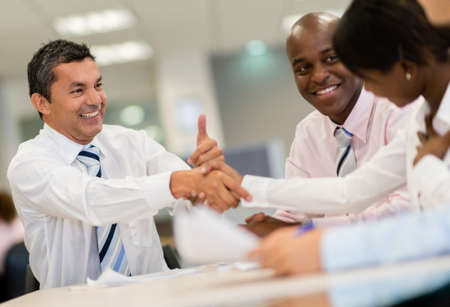 Successful group of business people closing deal with a handshake photo