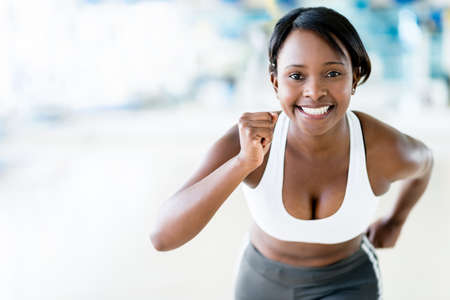 girl in sportswear: Competitive woman running at the gym looking happy