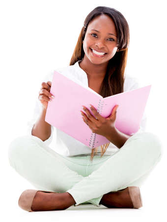 Female student smiling and sitting on the floor - isolated over white photo