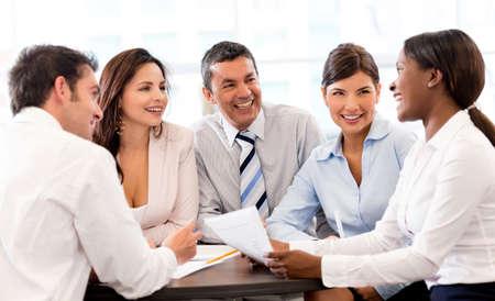 document management: Gelukkige mensen in een zakelijke bijeenkomst op het kantoor glimlachen