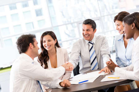 negotiation: Business handshake in the middle of a meeting at the office