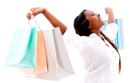 compras compulsivas: Mujer de compras feliz con los brazos arriba - aislados en fondo blanco