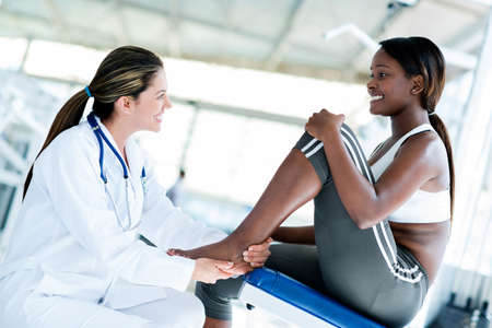 Gym doctor with a patient checking her ankle photo