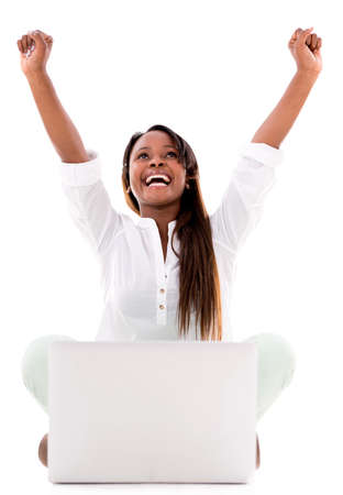 Woman celebrating her online success with a laptop - isolated over white photo