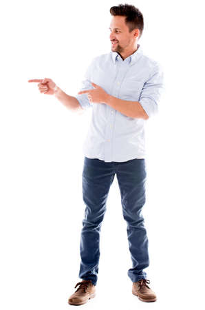 Casual man pointing to the side and smiling - isolated over white background photo