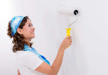 Casual woman painting a white wall with a paint roller photo