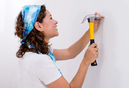 Casual woman hitting a nail in a wall with a hammer photo