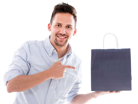Happy shopping man pointing at a bag - isolated over white photo