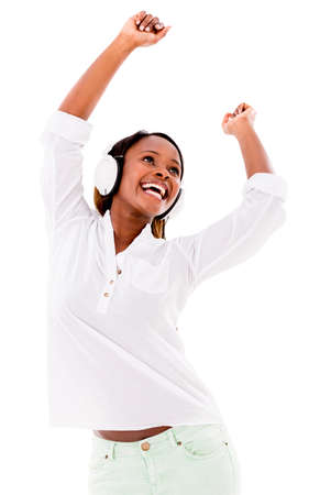 Happy woman dancing to the music with headphones – isolated over white photo