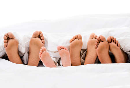 feet relaxing: Family in bed with their feet out  - isolated over white Stock Photo