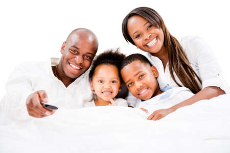 Happy family watching tv in bed - isolated over white photo