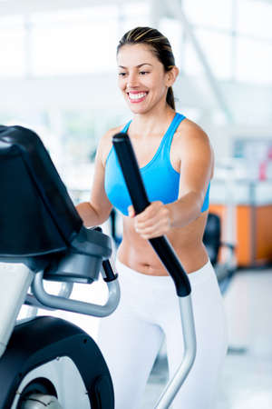 Beautiful woman exercising at the gym on an x-trainer Stock Photo - 20924728