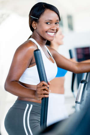 Happy woman exercising at the gym on an x-trainer Stock Photo - 20924735