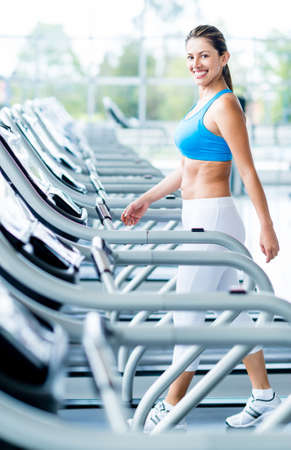 Woman walking on a treadmill at the gym Stock Photo - 20924736