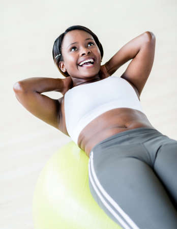 Happy woman at the gym exercising with a Pilates ball Stock Photo - 20924739