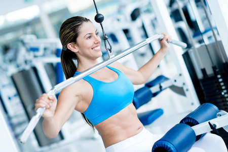 Beautiful woman exercising at the gym on a machine Stock Photo - 20924741