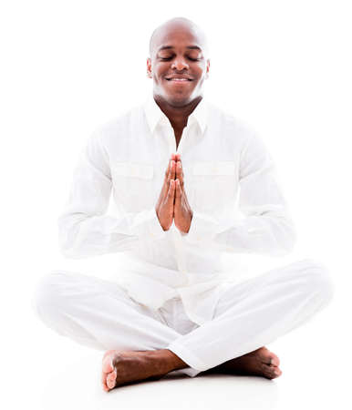 Peaceful man doing yoga exercises - isolated over a white background photo