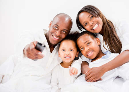 Happy family watching tv in bed - isolated over white Stock Photo - 20924470