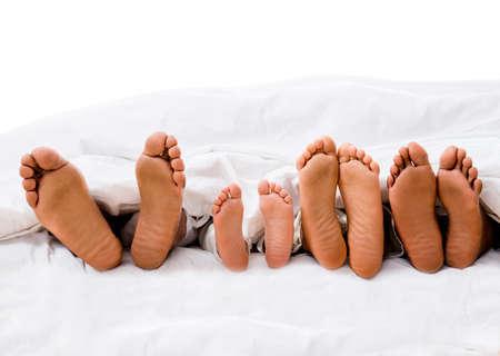 cama: Familia en la cama mostrando sus pies bajo las s�banas - aislado sobre blanco Foto de archivo