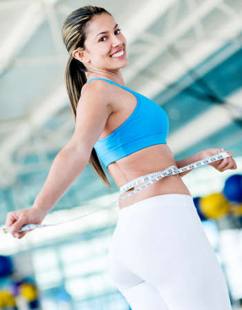 Gym woman taking measurements of her waist to ckeck her progress photo