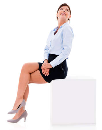 sitting on: Thoughtful business woman sitting on a cube - isolated over white Stock Photo