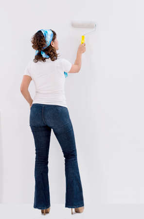 redecorating: Woman painting a white wall and redecorating her house