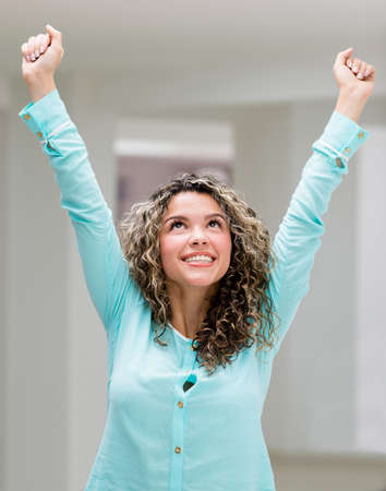 Successful business woman with arms up celebrating photo