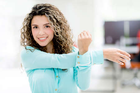 pause: Business woman stretching her arm at the office Stock Photo
